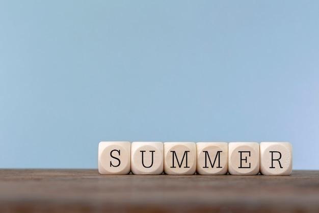 Palavra de verão escrita em cubo de madeira na mesa de madeira