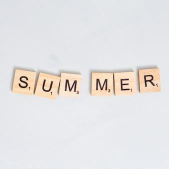 Palavra de verão escrita no bloco de madeira na superfície cinza