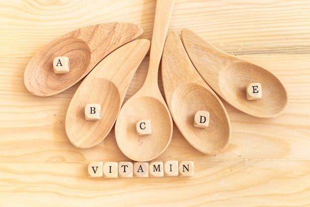 Palavra de vitamina vista superior feita de letras de madeira sobre a mesa e abcde na colher de madeira