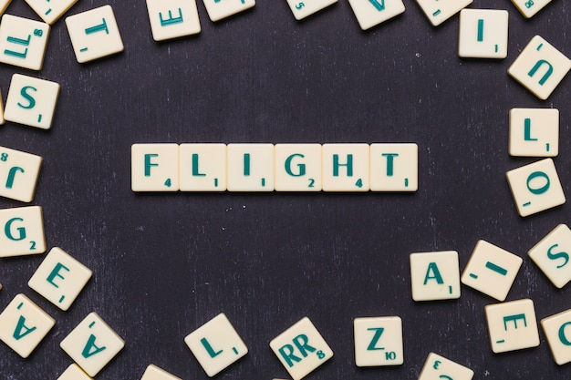 Palavra de voo organizada em fundo preto rodeado por letras scrabble