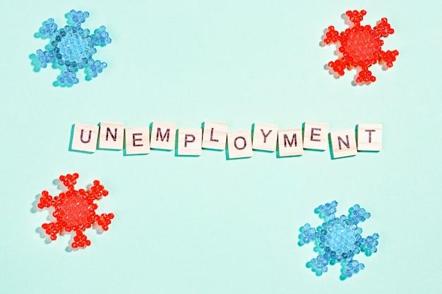 Palavra desemprego com modelos de coronavírus em fundo azul