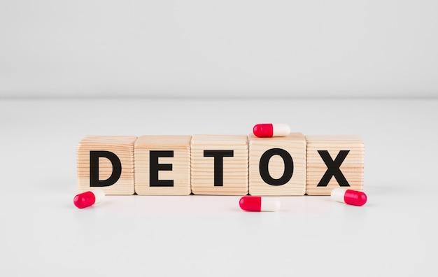 Palavra detox feita com blocos de madeira com pílulas vermelhas, conceito médico.