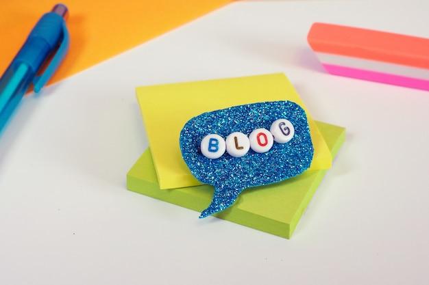 Palavra do blog de grânulos de plástico em um brilhante azul discurso bolha c acessórios de papelaria