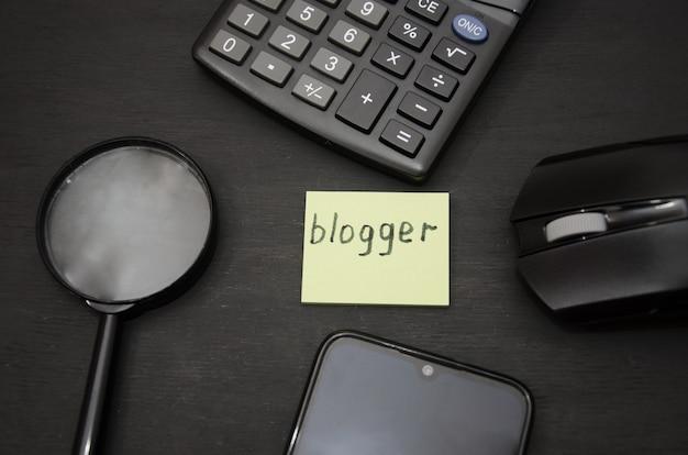 Palavra do blogger no adesivo lupa calculadora e smartphone no preto