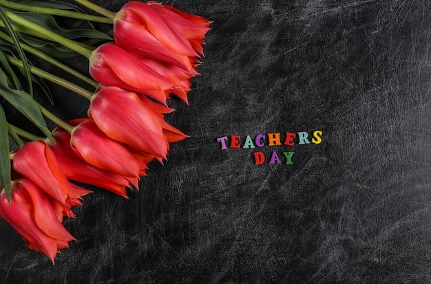 Palavra do dia dos professores. tulipas vermelhas no quadro de giz. vista do topo.