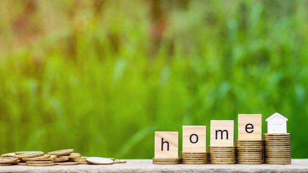 Palavra em casa na pilha de moedas e uma pilha de moedas de ouro na mesa de madeira.