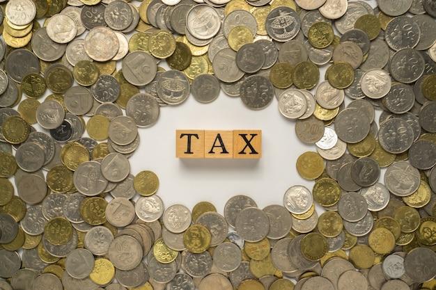 Palavra fiscal no bloco de madeira com uma pilha de moedas.