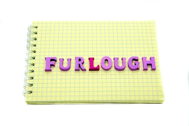 Palavra furlough disposto com letras de madeira no caderno com papel quadriculado amarelo. conceito de perda de emprego durante a pandemia de coronavírus, epidemia, isolamento social, coronavírus covid-19