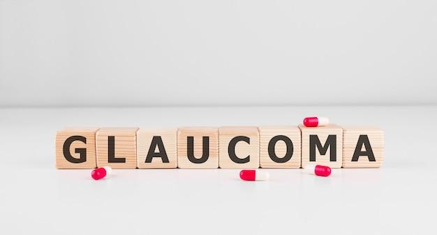 Palavra glaucoma feita com blocos de madeira com pílulas vermelhas, conceito médico.