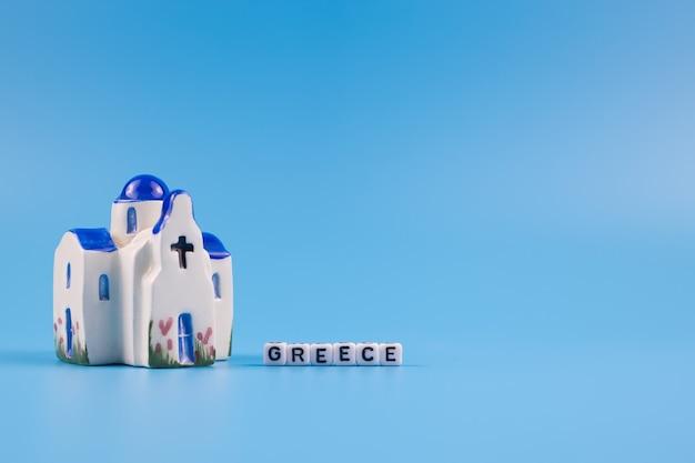 Palavra grécia e estatueta de uma capela grega, sobre fundo azul
