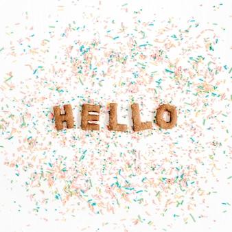 Palavra hello feita de letras de biscoitos doces em branco com confetes coloridos