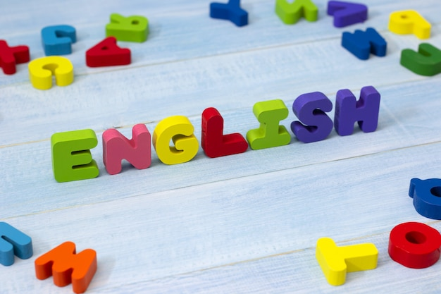 Palavra inglesa colorida de madeira no fundo de madeira azul.