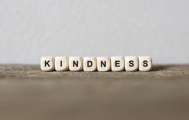 Palavra kindness feita com blocos de madeira, imagem de estoque