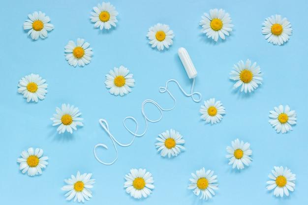 Palavra limpo de fio branco higiênico feminino tampão e chamomiles sobre fundo azul