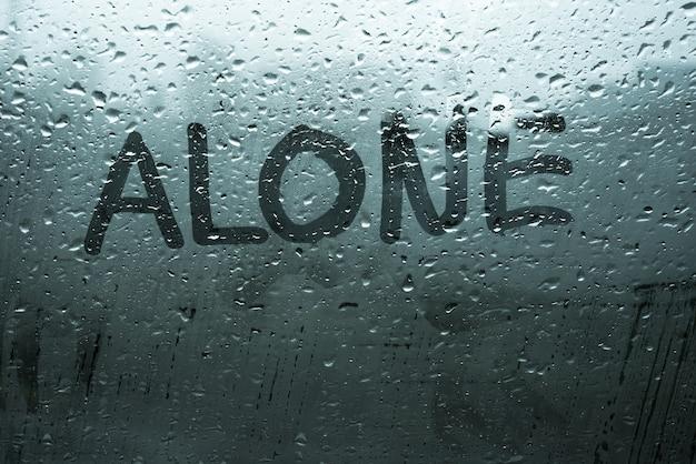 Palavra manuscrita sozinha no nevoeiro janela com gotas de chuva em tons frios