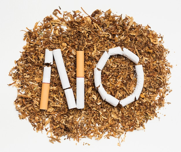 Palavra não feita de cigarro quebrado sobre tabaco