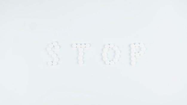 Palavra parar escrito com pílulas sobre fundo branco. pare o conceito de coronavírus.