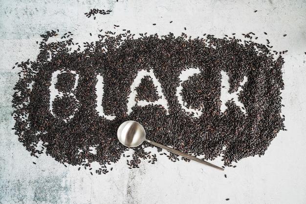 Palavra preta escrita em arroz selvagem e colher