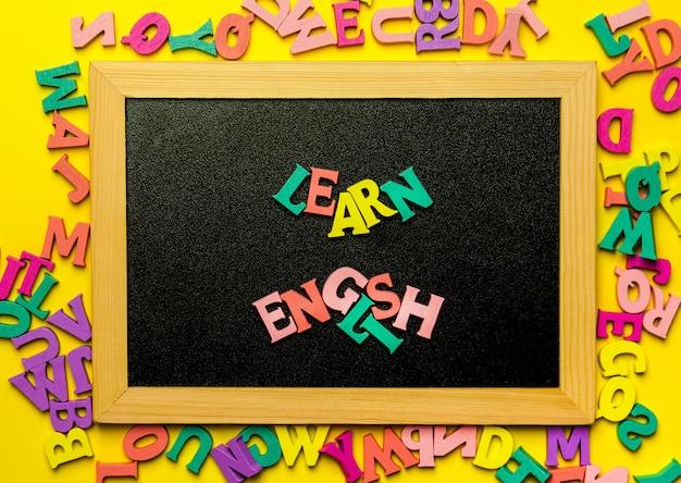 Palavra que aprende inglês feito com letras de madeira sobre a placa de madeira