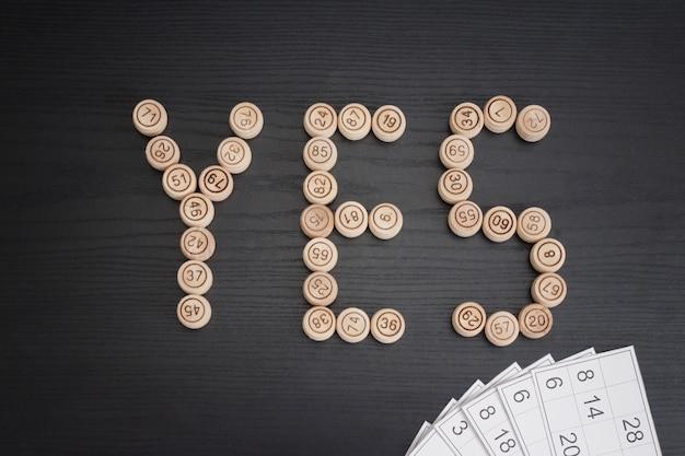 Palavra sim de barris de madeira. mesa de madeira preta. cartões de loteria
