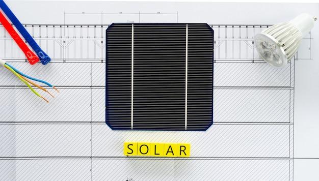 Palavra solar escrita em blocos de madeira amarelos com célula solar, lâmpada led e fios