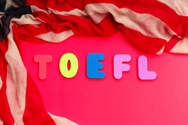 Palavra toefl e bandeira americana no exame de fundo vermelho eua
