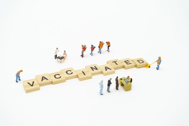Palavra vacinada em blocos com pessoas em miniatura