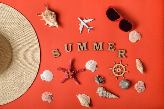 Palavra verão de letras de madeira. conchas, avião, parte de um chapéu, óculos de sol e volante. viva o fundo coral. postura plana. conceito de viagens