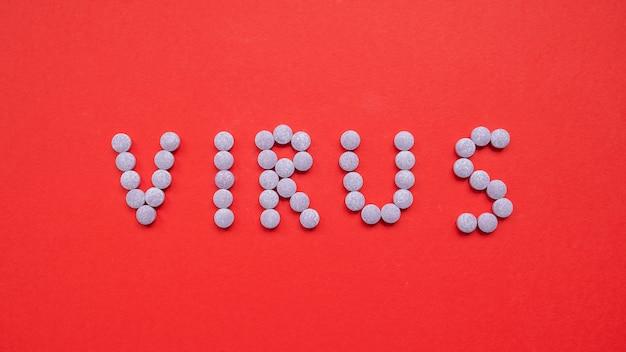 Palavra vírus escrito com pílulas sobre fundo vermelho. conceito de coronavírus. vista do topo