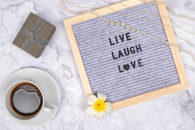 Palavra viver rir amor no quadro de cartas na mesa de mármore branca com uma xícara de café e caixa de presente