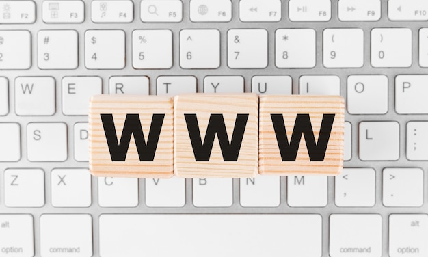 Palavra www em blocos de madeira com fundo de teclado.
