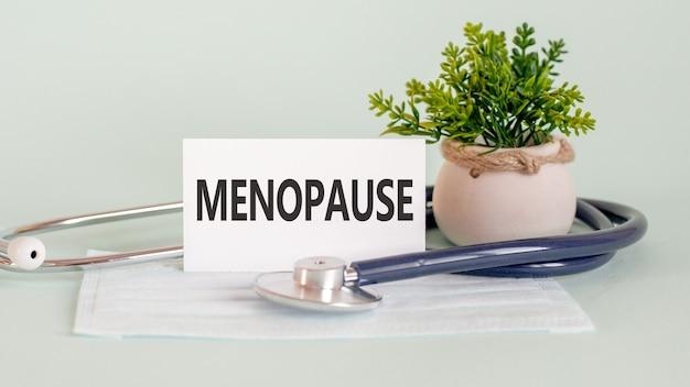 Palavras da menopausa escritas em uma ficha médica branca, com máscara de medicamento, estetoscópio e flor verde na parede