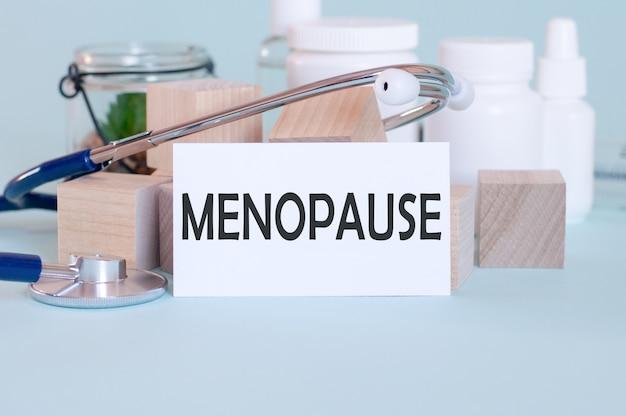 Palavras da menopausa escritas na ficha médica branca, com estetoscópio, flor verde, pílulas médicas e blocos de madeira