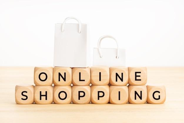 Palavras de compras online em blocos de madeira na mesa e sacolas de papel