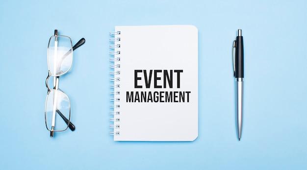 Palavras de gerenciamento de eventos no bloco de notas branco, caneta e óculos sobre fundo azul. conceito