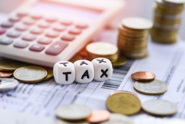 Palavras de impostos e moedas empilhadas calculadora em papel de bill fatura para preenchimento de imposto de tempo