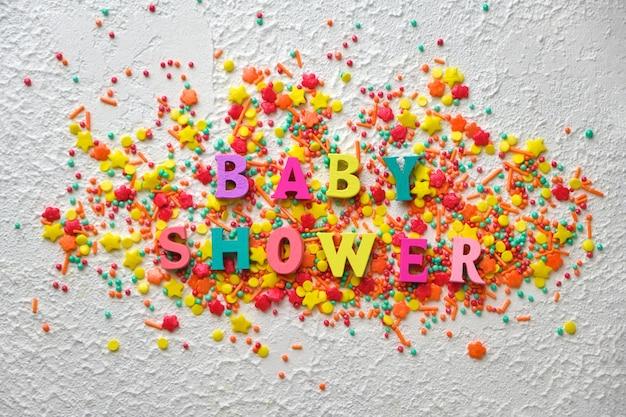 Palavras de madeira do chá de bebê em confetes coloridos, em plano de fundo texturizado branco