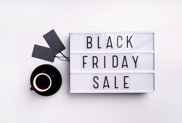 Palavras de venda da black friday na mesa de luz com uma xícara de café e etiquetas de preço pretas