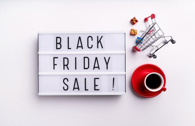 Palavras de venda da black friday na mesa de luz com uma xícara de café e vista superior do carrinho de compras