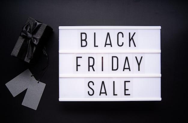 Palavras de venda de sexta-feira negra na mesa de luz com xícara de café, telefone celular e planta de vaso