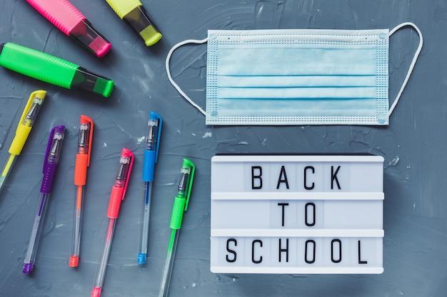 Palavras de volta à escola, máscara, canetas em fundo cinza. educação ou estudo durante o conceito covid-19 de coronavírus