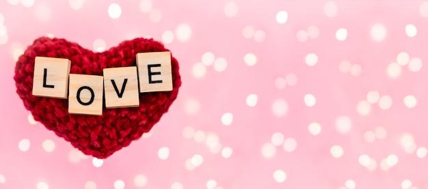Palavras do banner amor em coração de pelúcia vermelho fundo rosa desfocado
