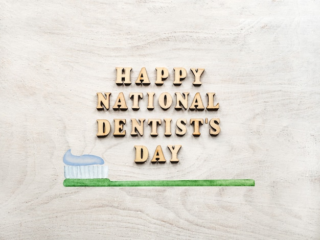 Palavras do dia do dentista com escova de dentes na mesa de madeira