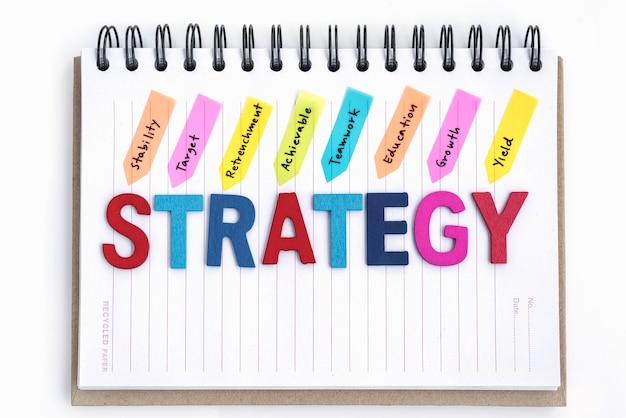 Palavras estratégia no caderno sobre o fundo branco