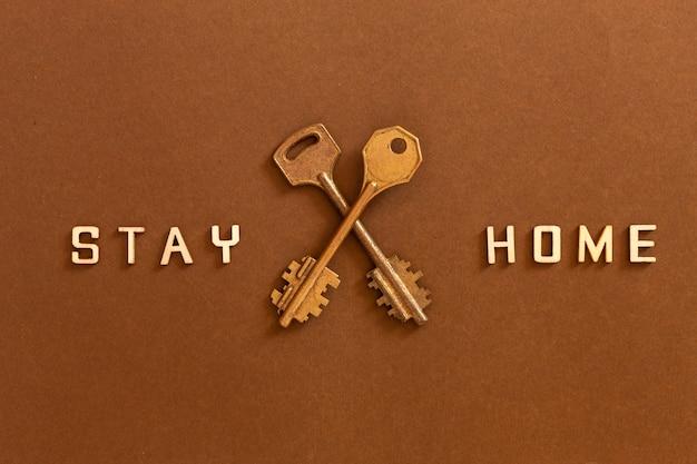 Palavras fique em casa feito de letras de madeira e duas chaves, conceito de auto-quarentena em casa como medida preventiva contra o surto de vírus de coroa covid 19.