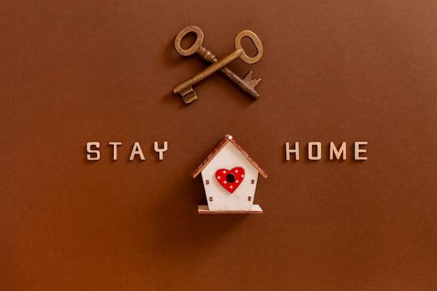 Palavras fique em casa feito de letras de madeira, figuras de casa e chaves, conceito de quarentena em casa como medida preventiva contra o surto de vírus de coroa covid19.