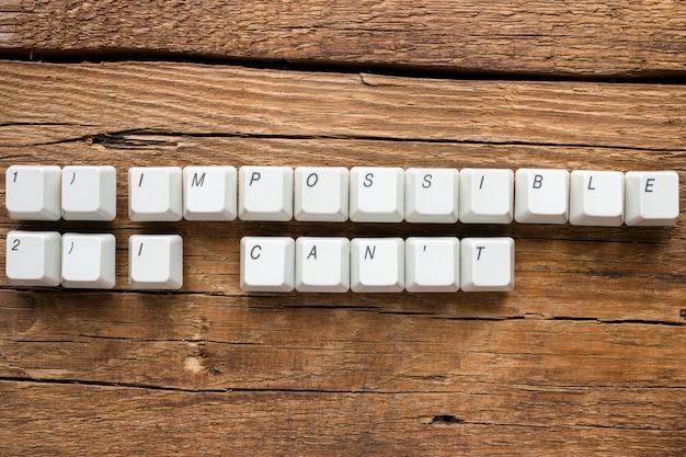 Palavras impossíveis e eu não posso das teclas do teclado em fundo de madeira