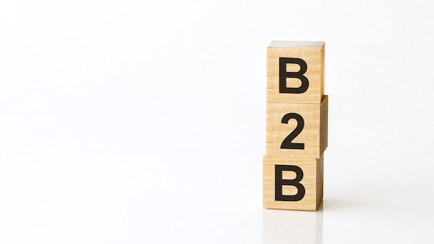 Palavras motivacionais: b2b em letras do alfabeto 3d de madeira em uma superfície branca brilhante