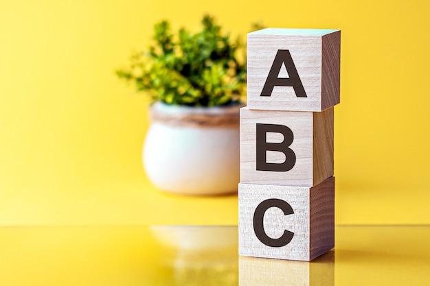 Palavras motivacionais: bpm em letras do alfabeto 3d de madeira em um fundo amarelo brilhante com espaço de cópia, conceito de negócio. bpm - gestão de processos de negócio. conceitos de vista frontal, flor ao fundo.
