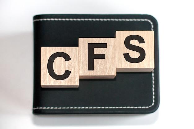 Palavras motivacionais: cfs em letras do alfabeto 3d de madeira em uma superfície de teclado